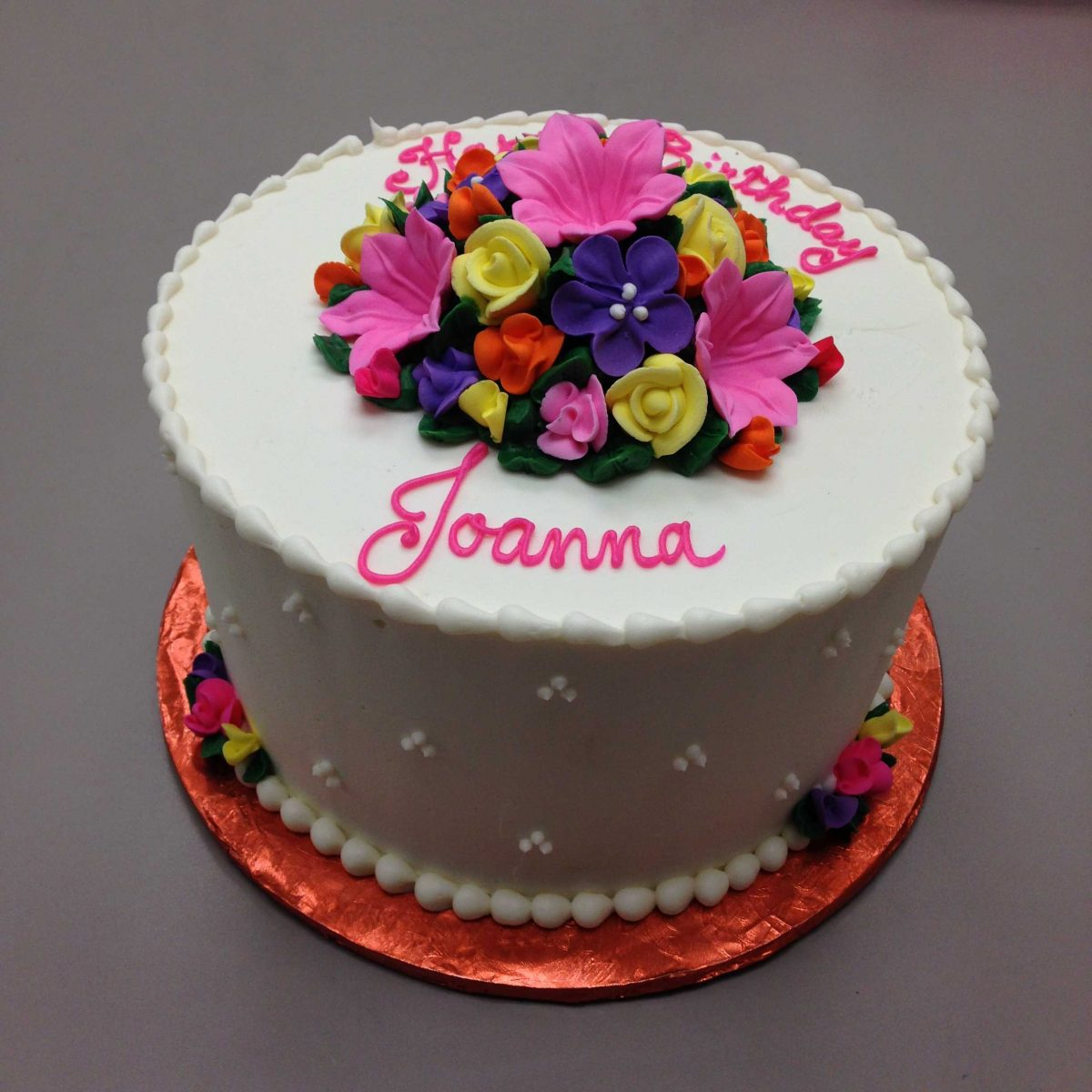 cluster of flowers on top of cake with triple dot design