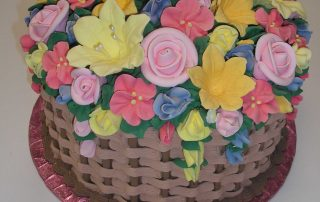 gift basket cake with mound of flowers covering top